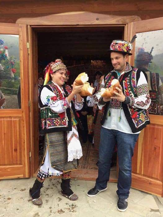 Couple breaking bread in traditional Ukrainian ceremony for elopement in Ukraine.
