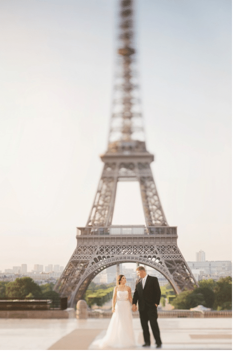 Romantic photo of couple underneath Eiffel tower in Paris. For more French wedding inspiration, find out more about elopements in France.