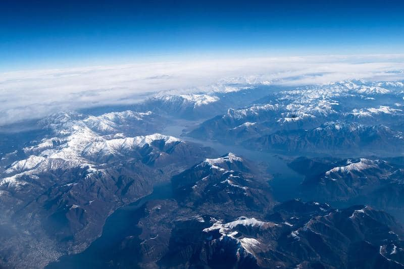 Photo of mountains from airplane. Find out how to relief IBS while traveling and what to know before you travel with irritable bowel syndrome.