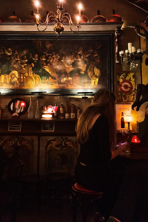 Girl enjoying a date at a brown bar in Amsterdam. One of the most romantic things to do in Amsterdam is to go for a jenever tasting together! #amsterdam