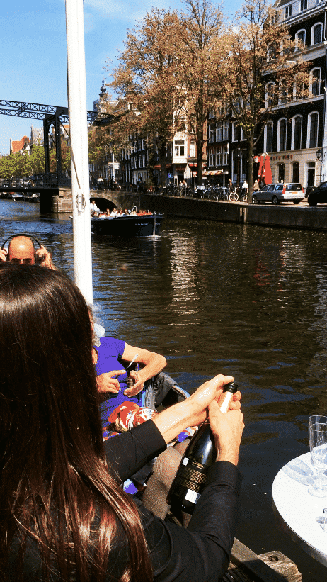 Couple opening a bottle of champagne along the canals of Amsterdam; This is one of the most romantic things to do in Amsterdam! #amsterdam #travel