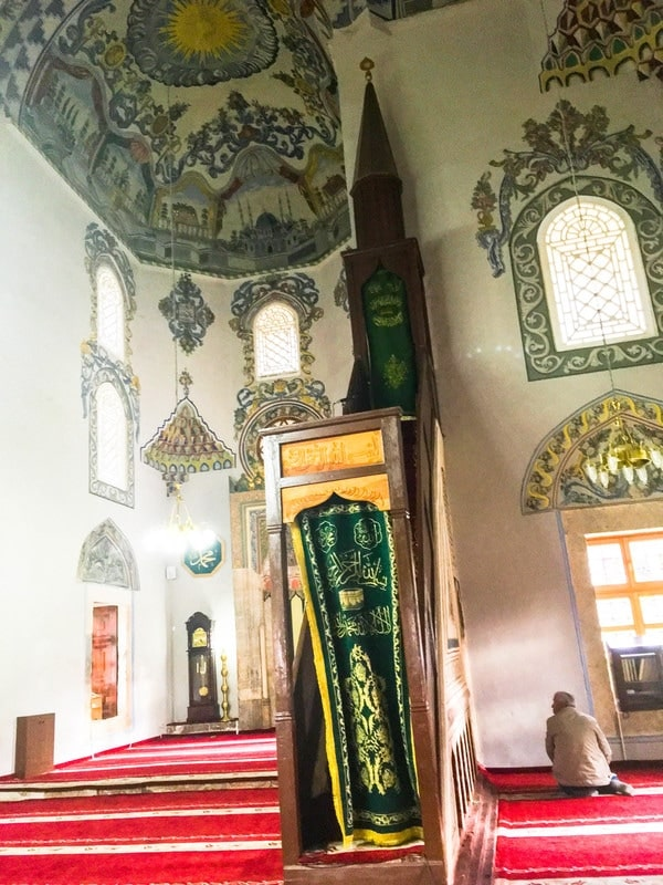 Man praying in the Sinan Pasha Mosque in Kosovo. See why you should visit Prizren Kosovo in the Balkans with photos of Kosovo #Prizren #travel #Balkans