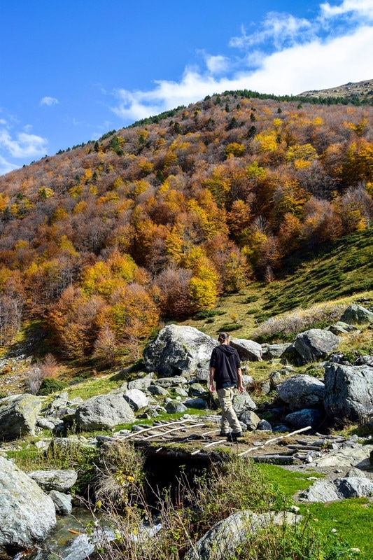 Photo of man on bridge in mountains in Kosovo. See why you should visit Kosovo in fall with beautiful photographs of Kosovo. #fall #Kosovo #Balkans #fall