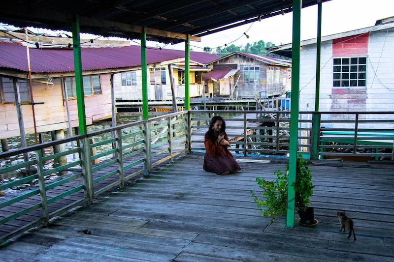 Girl with kittens in Kampong Ayer water village in Brunei. See why you should visit Brunei with the best things things to do in BSB!