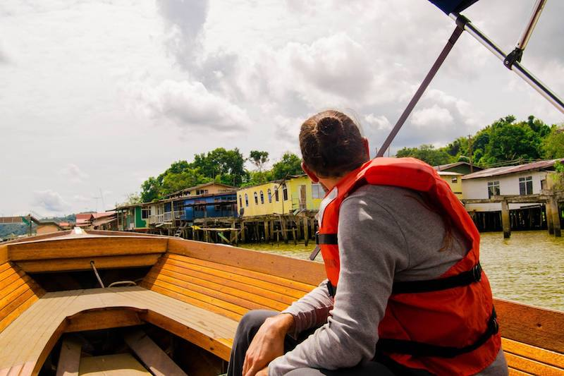 Man on water taxi in Bandar Seri Begawan. Read about the best attractions to see in Bandar Seri Begawan and why you should visit Kampong Ayer!