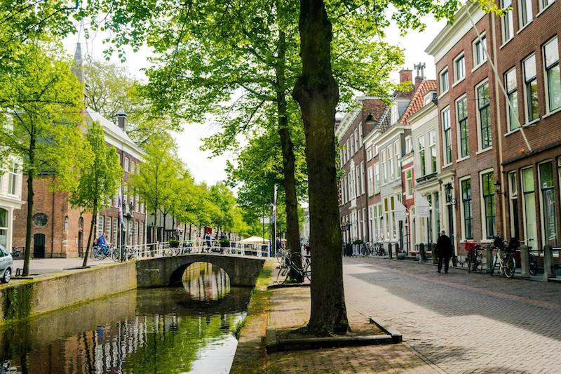 Photo of Oude Delft canal in Delft. This beautiful canal is a must-see in Delft, one of the cities that you need to visit in the Netherlands! Be sure to include it in your itinerary! #Netherlands #Delft #Travel