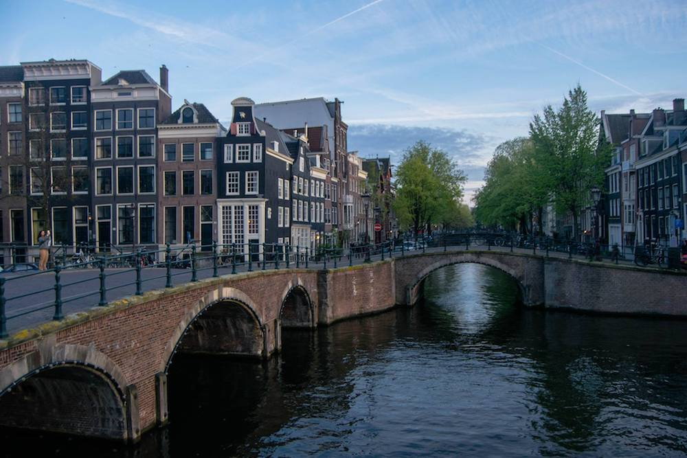 Photo of canals of Amsterdam. Read tips for the best things to do in Amsterdam on a budget with insider tips for the best free things to do in Amsterdam. #travel #Netherlands #amsterdam