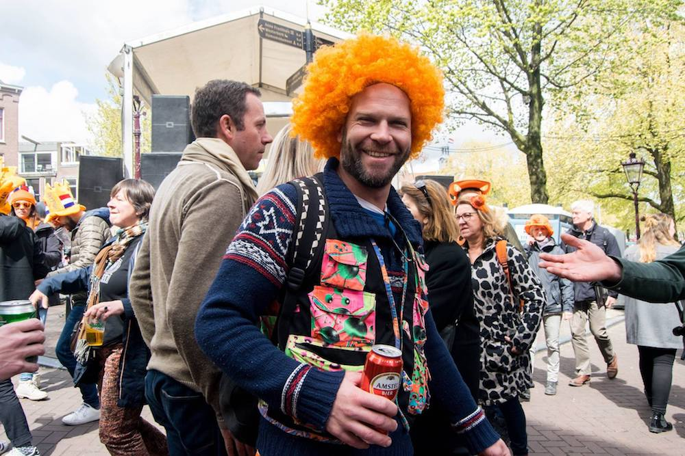 Man dressed up for King's day in Amsterdam. Read tips for celebrating King's Day in Amsterdam, the Netherlands!