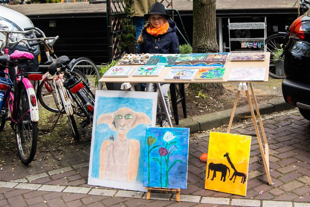 Girl selling street art on the street on King's Day in Amsterdam. Read tips for celebrating Koningsdag in Amsterdam! #Amsterdam #Netherlands