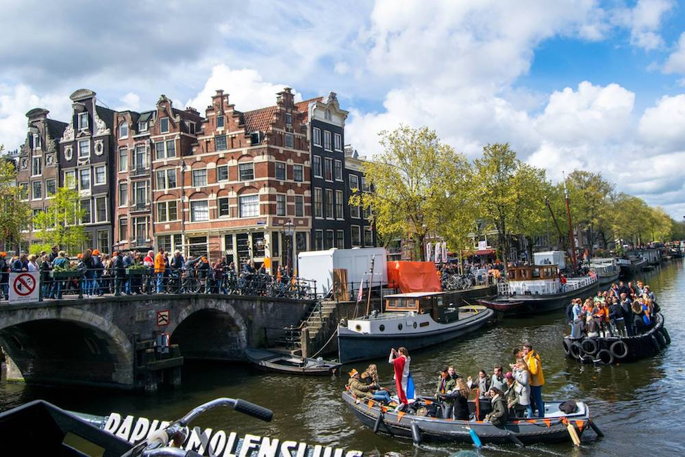 Boat in canal on King's Day in Amsterdam, the best holiday in Amsterdam. Celebrate this holiday this spring in Amsterdam with insider tips! #amsterdam #Netherlands #travel #europe