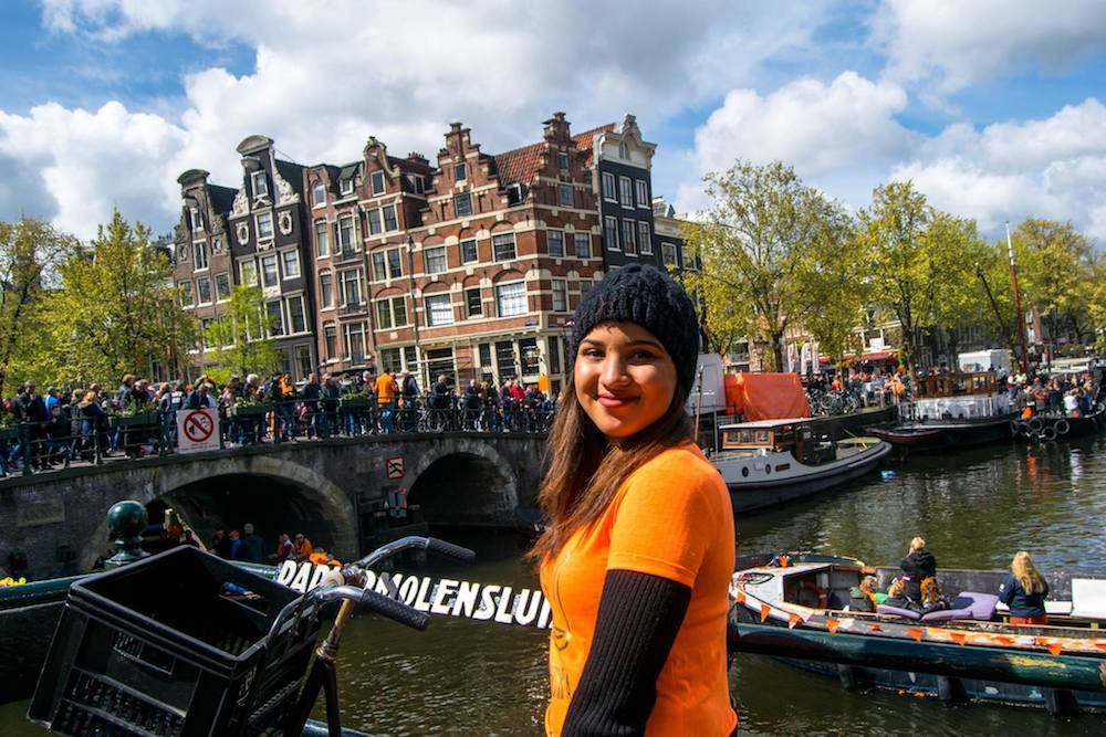 Girl dressed up for King's Day in Amsterdam, the Netherlands. King's Day is one of the best Dutch holidays to celebrate. Read tips on what to know before visiting Amsterdam for King's Day! #Amsterdam #Netherlands #travel