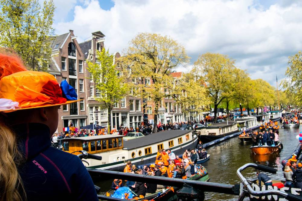 Canals of Amsterdam on Koningsdag, King's Day, in Amsterdam. This Dutch holiday is one of the best times of the year to visit in Amsterdam! #Amsterdam #Netherlands #travel