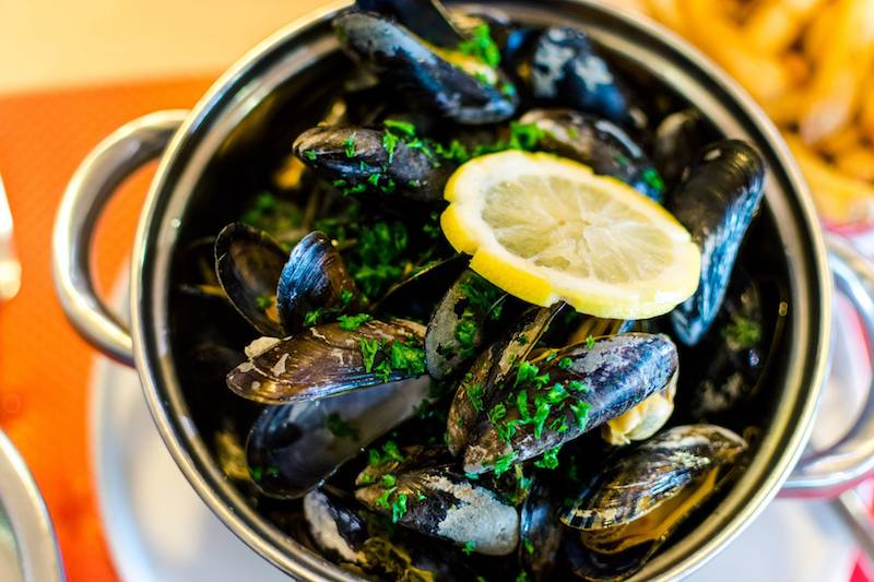 Mussels cooked in Calvados, one of the best budget meals to eat in Normandy France. Read more insider tips for traveling around France on a budget! #france #travel #food