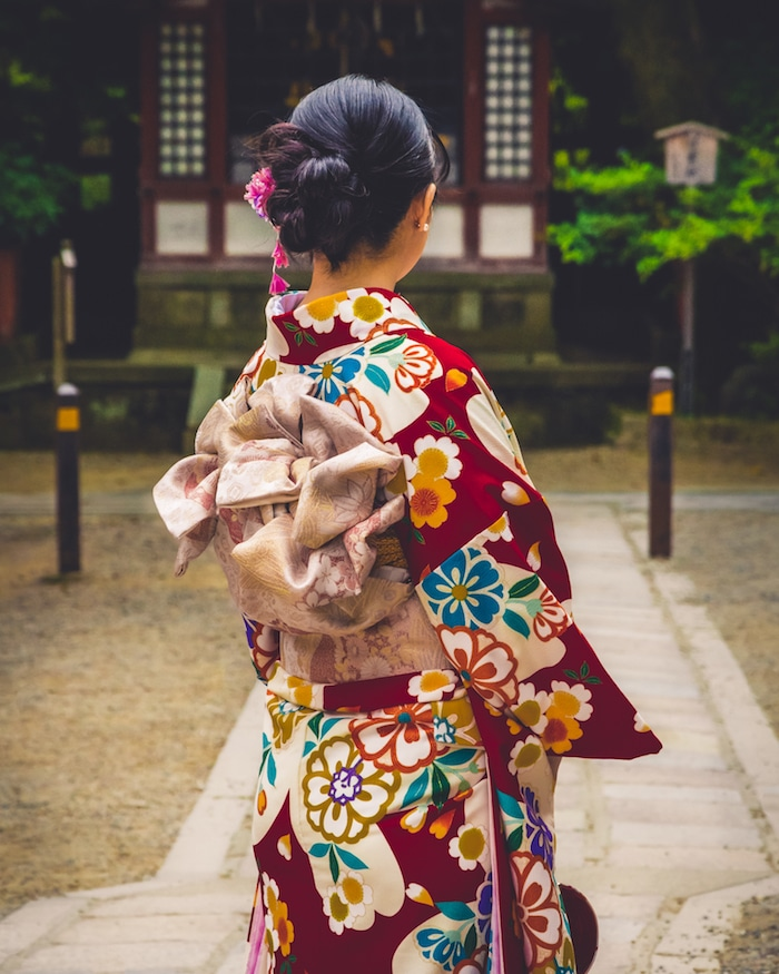Photo of girl at a shrine in Kyoto. Read tips for the best shrines in Kyoto to visit for getting off the beaten path in Kyoto with tips for visiting the most beautiful temples in Kyoto. #travel #kyoto #japan #asia