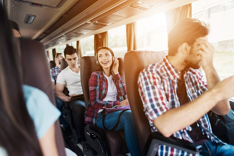 Girl sitting on a bus. Read tips for traveling without a car in the United States and what to know about bus companies in the United States.