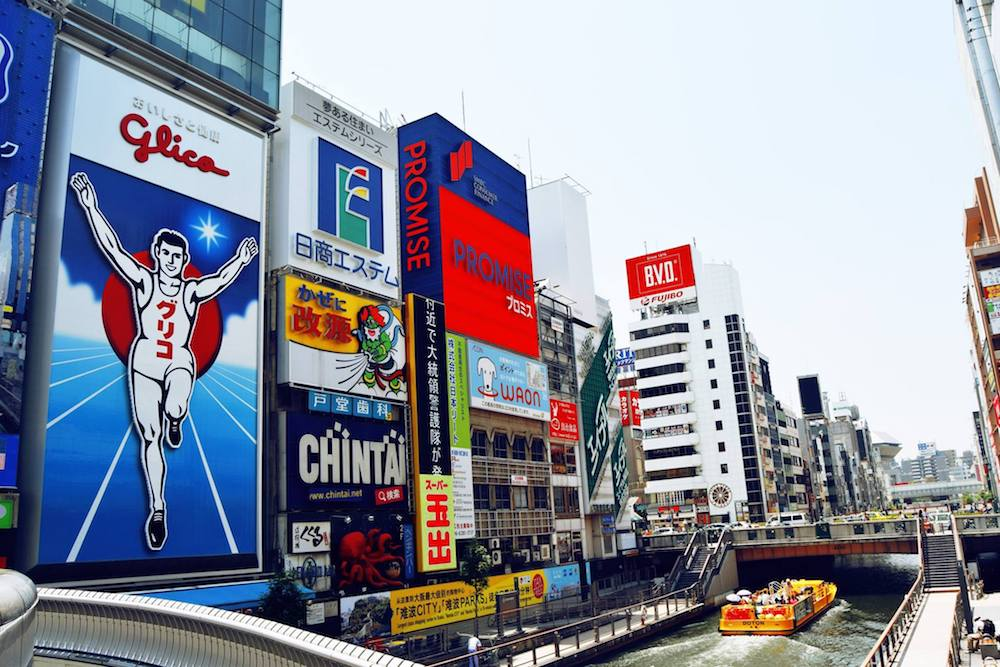Glico Man in Osaka Japan. This iconic sight is one of the best things to do in Osaka Japan. Read more Osaka travel tips in this Osaka travel guide. #Osaka #travel #japan