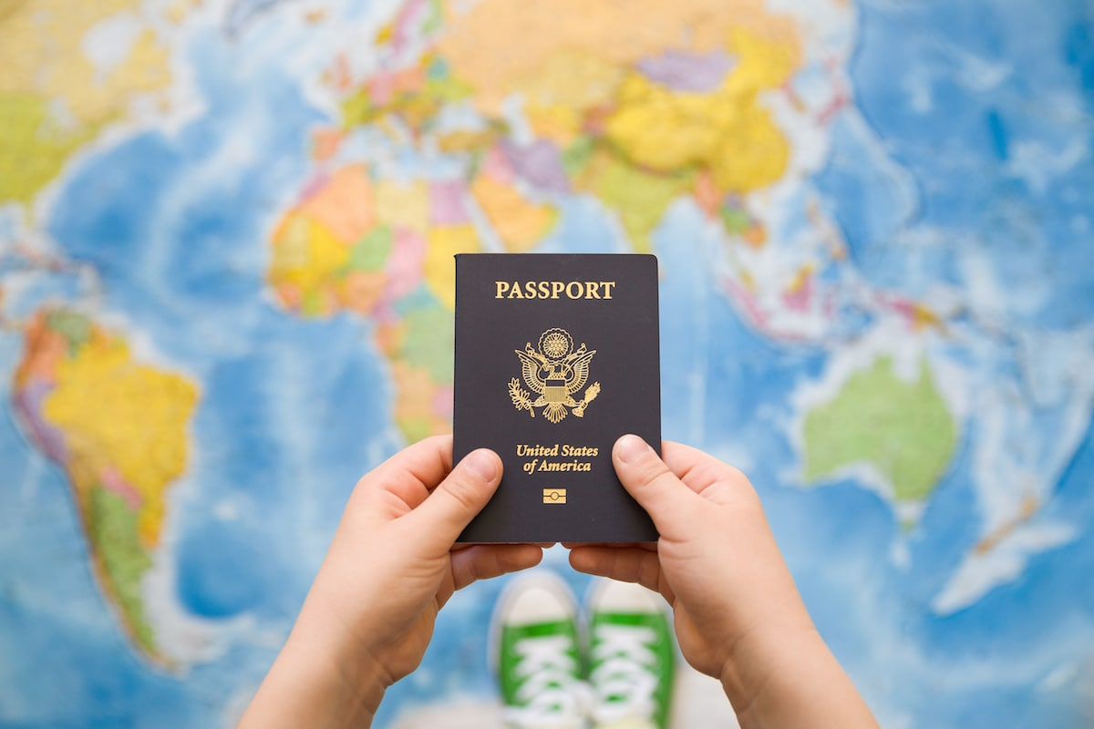 Child's hand holding US passport. Read about passport privilege and traveling with a weak passport!