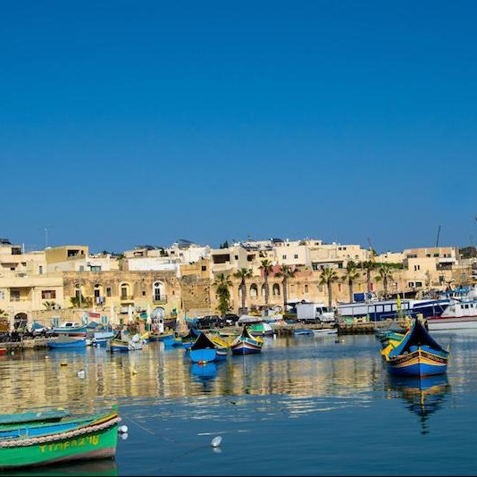 Boats in Marsaxlokk, a fishing town in Malta. This beautiful town must be included in your trip to Malta, even if you're traveling to Malta without a car! Read tips for visiting Malta without a car! #travel #Malta #Europe #Marsaxlokk