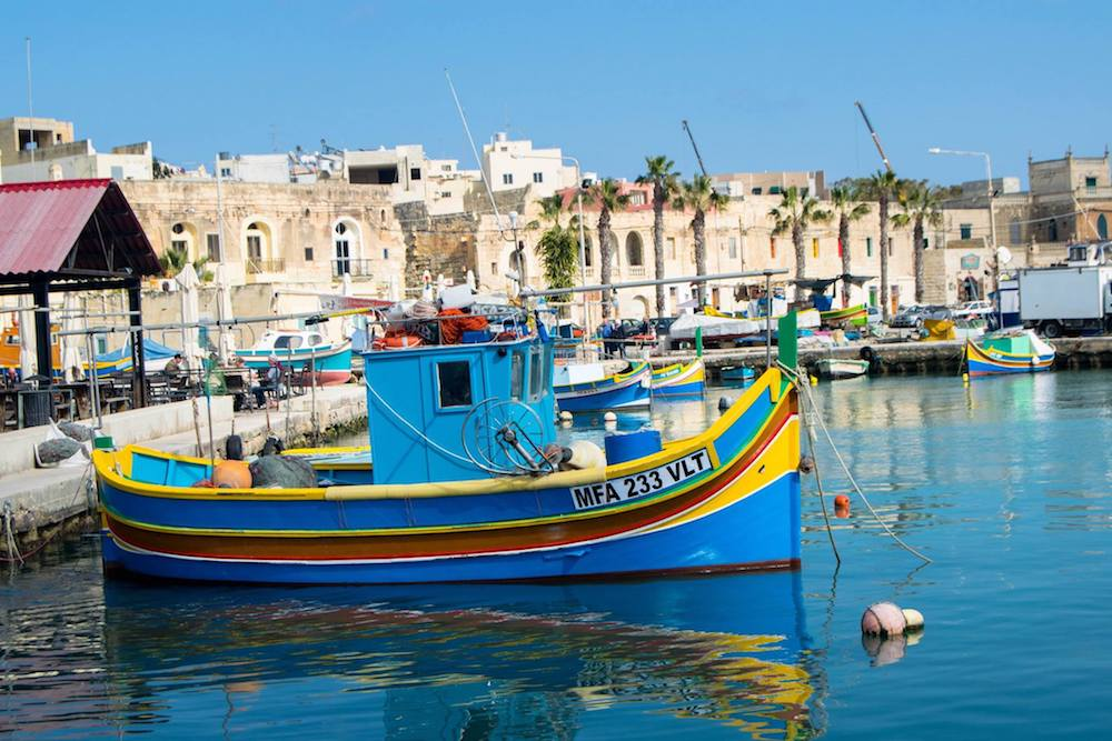 Traditional Maltese boats in Marsaxlokk, one of the most beautiful cities in Malta. Read why you must include Marsaxlokk in your Malta itinerary! #travel #malta #Marsaxlokk #europe #beautifulplaces