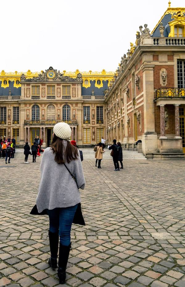 Girl walking on the grounds of Versailles. Read tips for visiting Versailles, how to avoid the crowds at Versailles, and what to know before your visit to Versailles! #travel #versailles #france