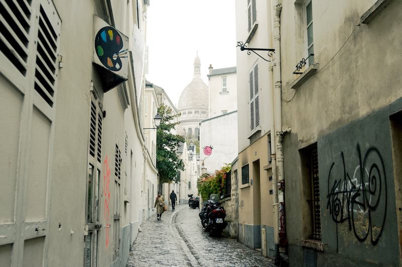 View of streets in Montmartre, a former village in Paris. This former village is perfect for a long walk. Read the perfect two hour itinerary for exploring Montmartre (the 18th arrondissement of Paris). #travel #Paris #Montmartre