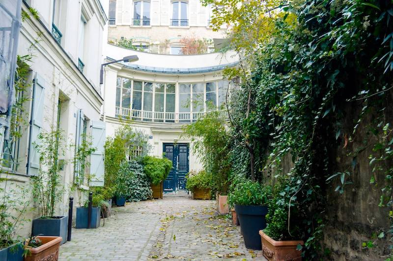 Leafy secret street in Paris in Cité du Midi. This beautiful hidden village in Pigalle should not be missed on your trip to Montmartre! #travel #Paris #France