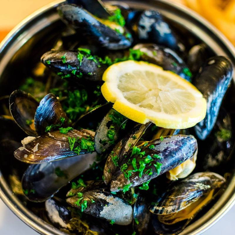 Mussels cooked with calvados in Fécamp, a coastal town in Normandy. Read what to do in four days in Normandy with the perfect itinerary! #travel #food #mussels #normandy #calvados
