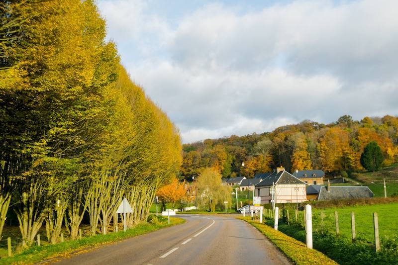 Scenic road with chateau in Parc Naturel Régional des Boucles de la Seine, one of the most beautiful places to visit in Normandy. This beautiful park makes for a scenic road trip in Normandy! #travel #Normandy #france
