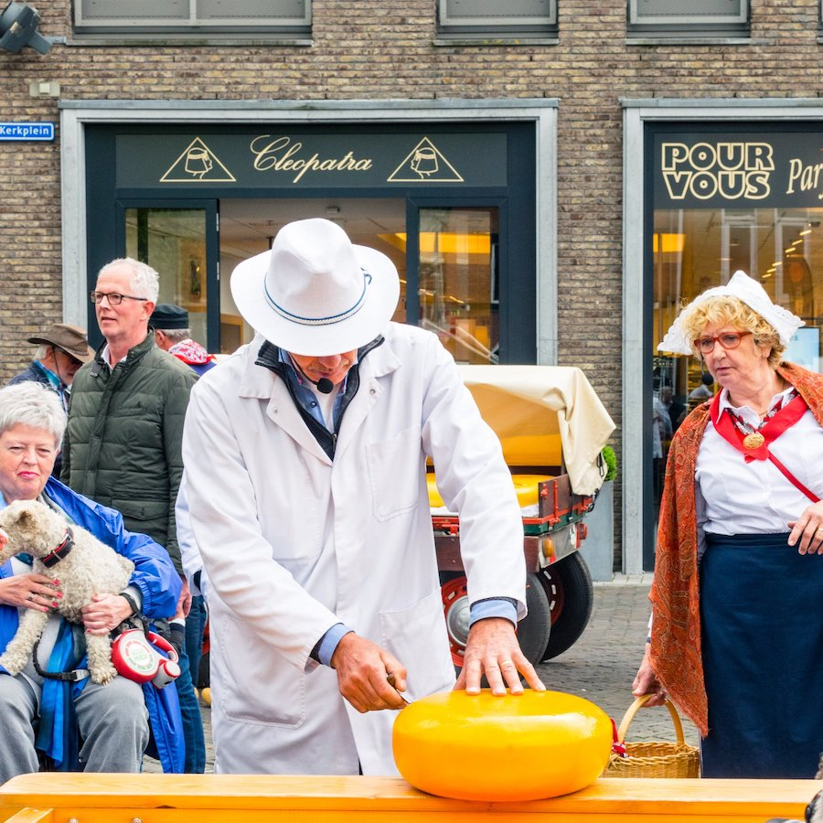 Merchant tasting the cheese at the Woerden kaasmarkt, one of the Dutch cheese markets. This one is 100% real! #travel #netherlands #cheese #gouda