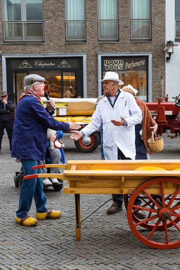 Two men at a Dutch cheese market in Woerden. This authentic Dutch cheese market is a must for your bucket list in the Netherlands. Be sure to include a half day in Woerden in your itinerary!