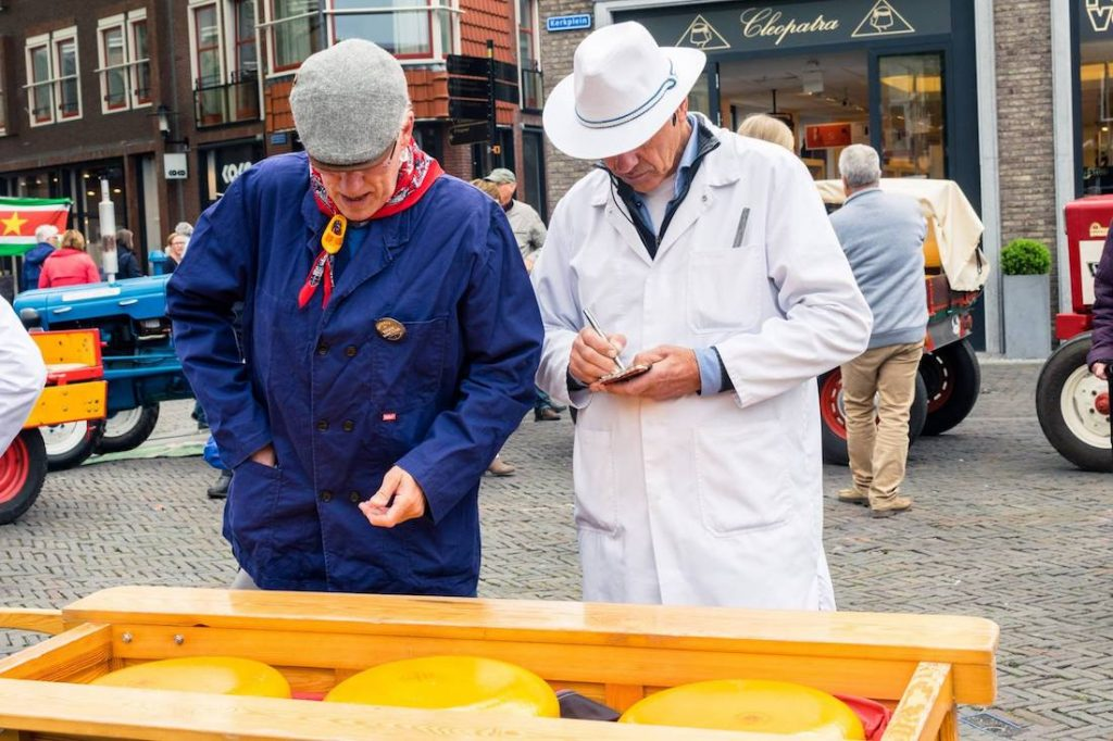 Seller buying the cheese at the Woerden cheese market, a historic cheese market in the Netherlands. The Woerden kaasmarkt is one of the last real cheese markets. #travel #cheese #gouda #netherlands