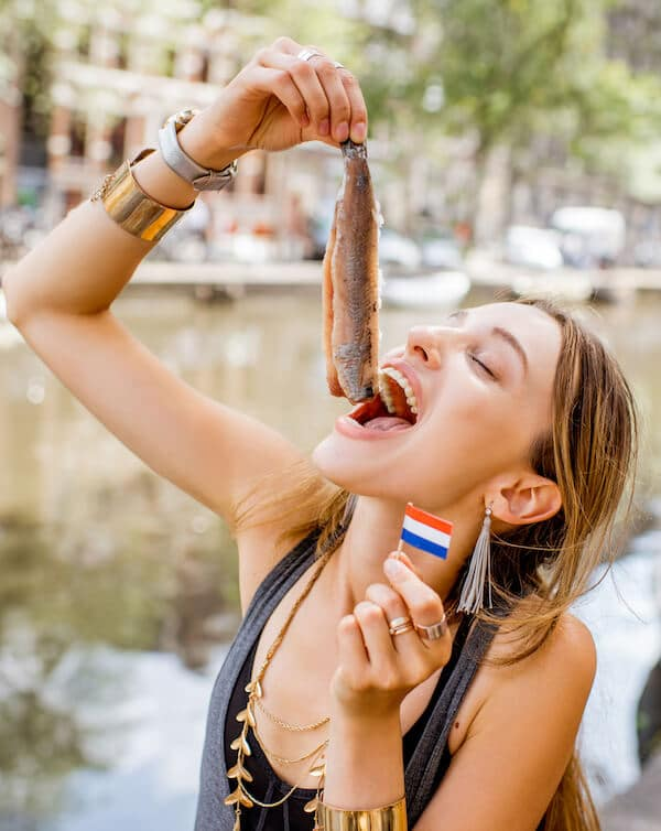 Girl eating herring in Amsterdam, the Netherlands. Read about Dutch foods that you must try in Amsterdam, the Netherlands! #travel #netherlands #holland #amsterdam