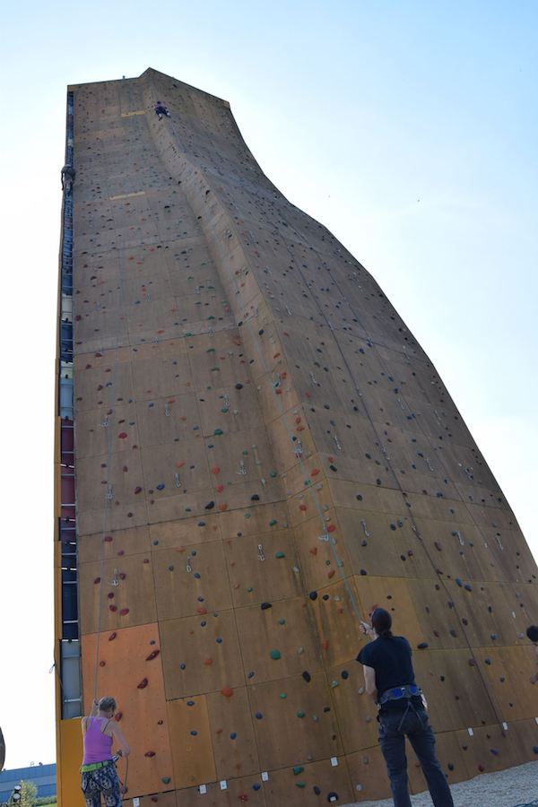 Man belaying on Excalibur Climbing Wall, one of the craziest climbing walls in the world. Read why you must put this climbing activity on your bucket list! #travel #climbing #adventuretravel