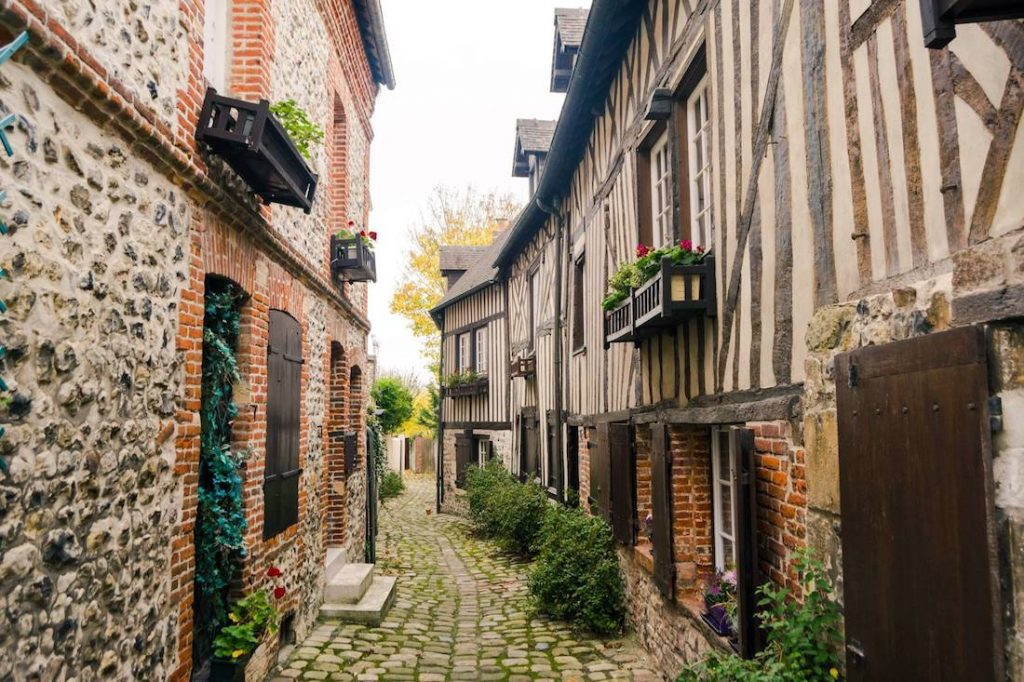 Beautiful city of Honfleur in France. Read what to bring to Europe for two weeks in this guide by an American expat in Europe who travels carry-on in Europe. Your ultimate guide to packing light for Europe! #travel #europe #france #honfleur