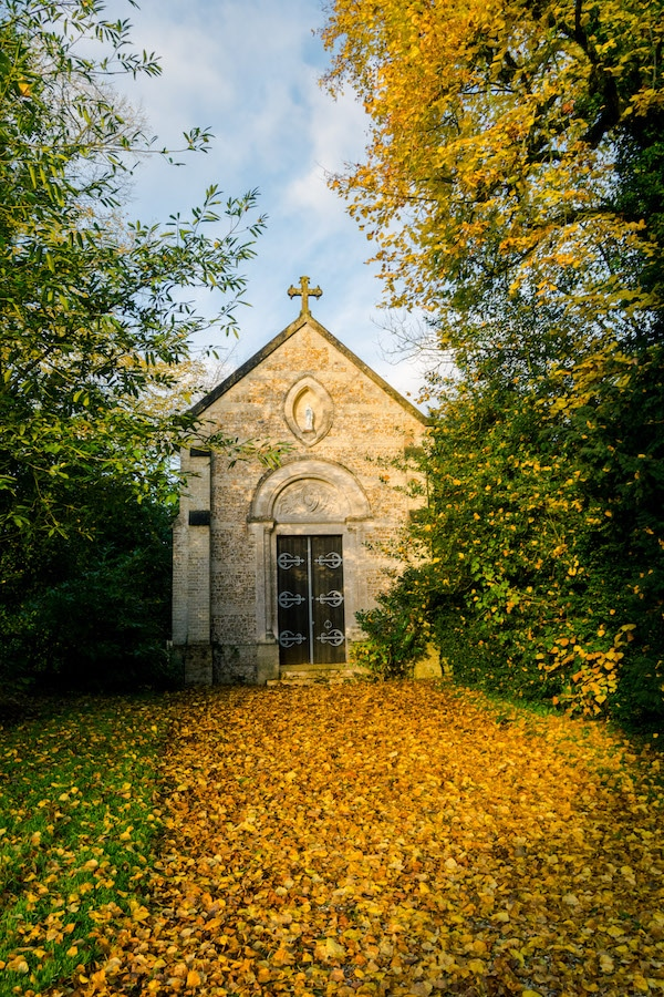 Fall leaves surrounding the family chapel on the grounds of a chateau in France. Read about seven chateaus in France that you can stay at! #travel #france #Normandy