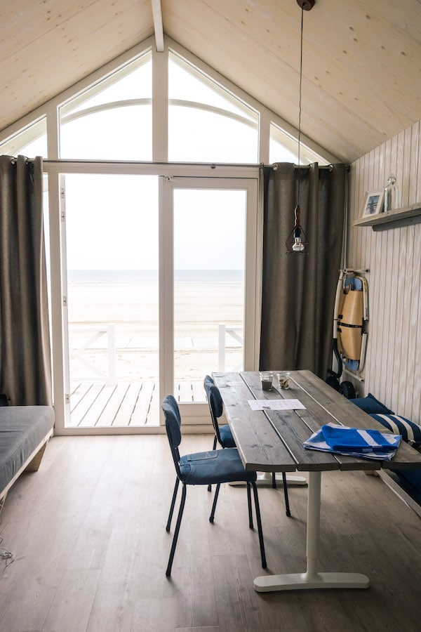 View of the beach from inside the Haagse Straandhuisjes, one of the luxurious options for hotels near Scheveningen! #travel #hotels #beach #holland