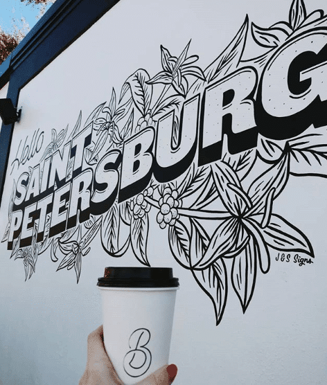 Coffee with mural with backdrop of St. Petersburg mural in St. Pete, Florida. Read about the best places to eat in St. Pete in this guide to St. Pete! #travel #florida