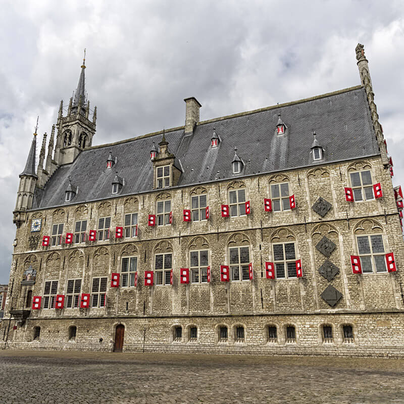 Side view of the Gouda City Hall, one of the most beautiful city halls in the Netherlands. Consider taking a day trip from Amsterdam to see this beautiful building. #travel #netherlands #holland