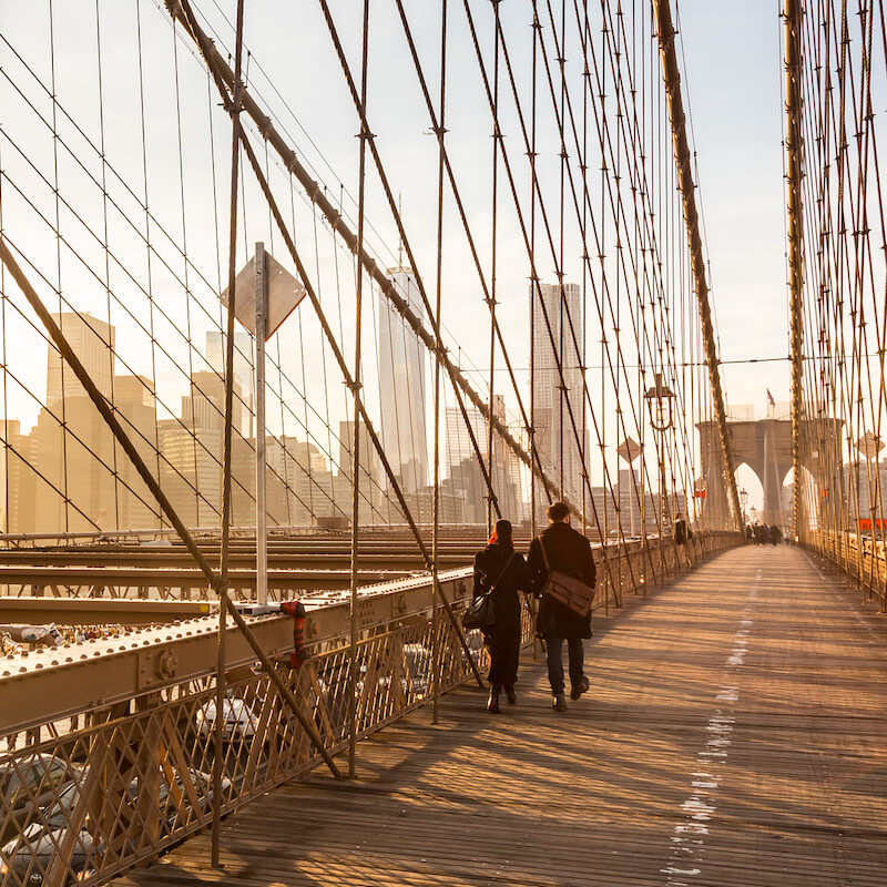 Couple walking over Brooklyn Bridge from Manhattan to Brooklyn. Read about what to do in downtown Brooklyn in this insider guide to downtown Brooklyn! #travel #brooklyn #NYC