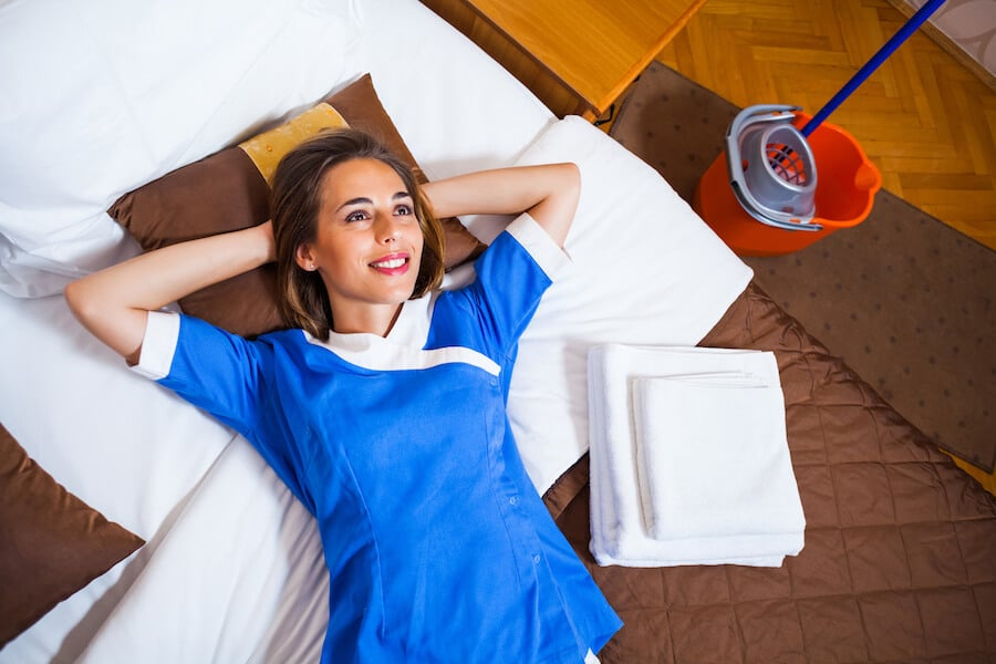 Housekeeper day dreaming in a hotel room. Read what not to do while staying at hotels! #travel #hotels
