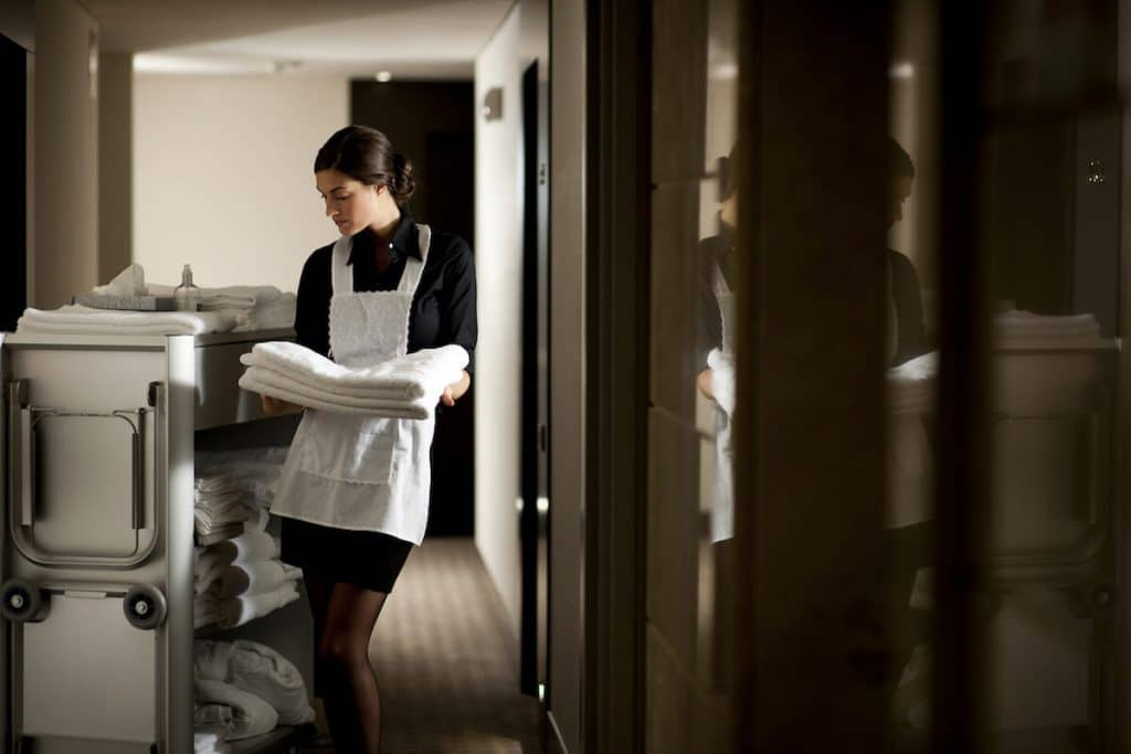 Hotel maid with cart refilling a room. Read what to do when staying a hotels.