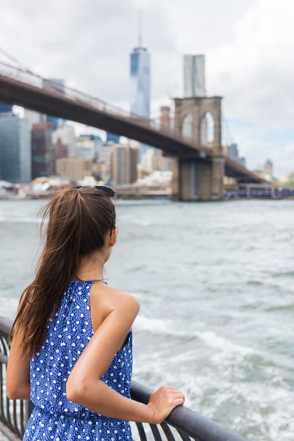 Girl admiring the Brooklyn Bridge from Brooklyn Bridge Park. Read what to do in Brooklyn in this guide to downtown Brooklyn! #travel #NYC #Brooklyn