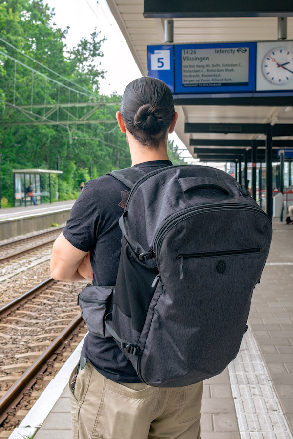 Photo of a man wearing the Tortuga Setout Backpack, one of the best travel backpacks for carry-on travel. #travel