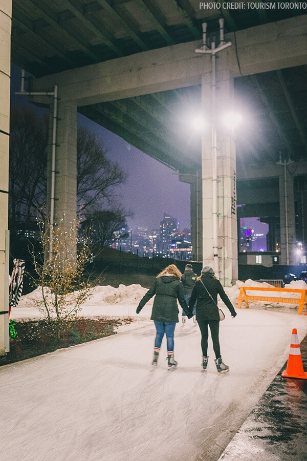 People ice skating on the Bentway Skating Trail in Toronto, Canada. The Bentway Trail is one of the best things to do in Toronto in winter! #toronto #canada #travel (Photo by Tourism Toronto)