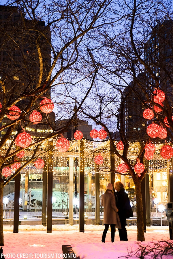 Couple enjoying the lights in the snow in Yorkville, Toronto, Canada. Read about the best things to do in Toronto in winter. #toronto #canada #travel (Photo by Tourism Toronto)