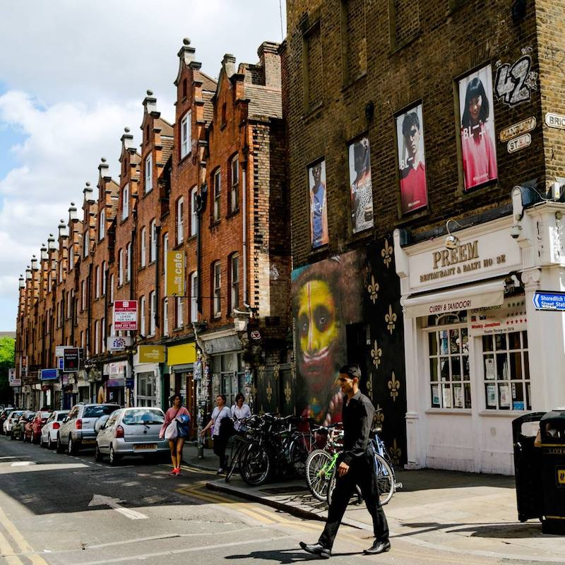 Man walking across the street close to Brick Lane, this diverse neighborhood in London is perfect for a stroll! #london #travel