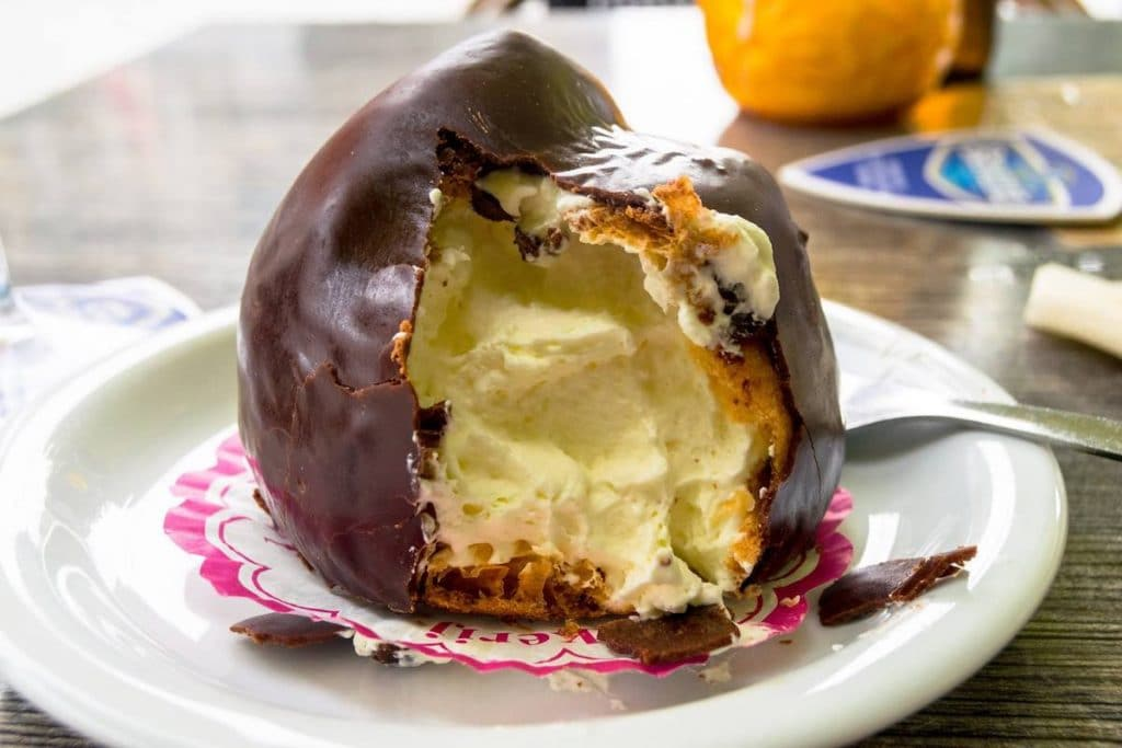 Bossche bol, one of the traditional foods in Den Bosch, the Netherlands. This Dutch sweet is a must-try in Brabant! #travel #denbosch #netherlands #nederland