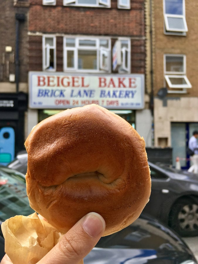 Woman holding a beigel from a famous eatery in London. Read your perfect one day guide to London! #travel #london