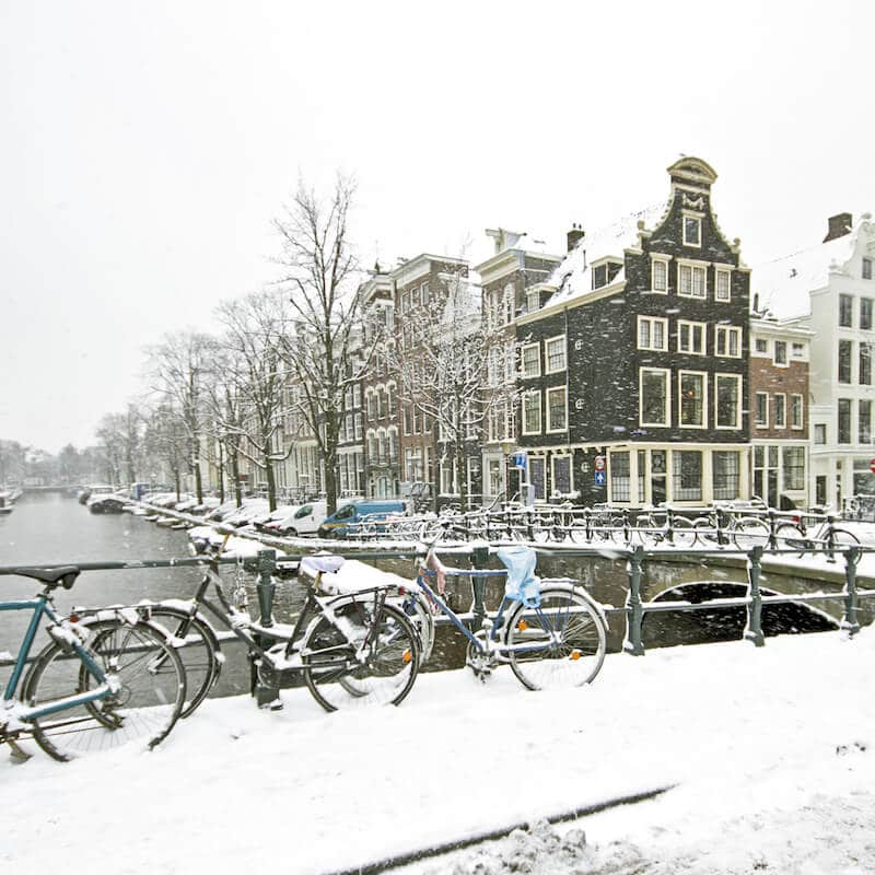 Snowy canal in Amsterdam during winter. Read about the best things to do in winter in Amsterdam. #amsterdam #netherlands