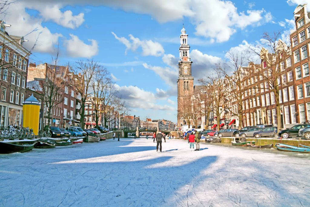 People ice skating in Amsterdam in winter. It's very rare that canals in Amsterdam freeze, but ice skating is one of the best things to do in Amsterdam in winter! #travel #amsterdam